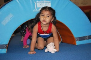 Gauri Sharma, 3, daughter of Massachusetts Gymnastics staff member Gargi Sharma, tries out some of the equipment in the preschool program. Photo/courtesy of Leo Doran