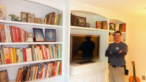 Raymond Valois, owner of Valois Home Improvement, stands near a bespoke built-in bookcase Photo/Melanie Petrucci