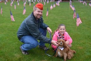 Marine Corps veteran Larry Minton poses with Patriots fan Buddy and Ellie Heald on the flag bedecked lawn of the Heald Chiampa Funeral Home in the center of Shrewsbury. Photo/Joyce DeWallace