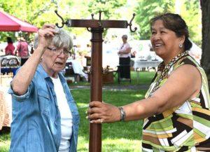 Sheila Dickman and Linda Casey examine an antique coatrack. Photos/Ed Karvoski Jr.