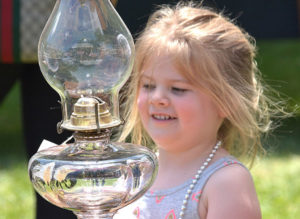 Jenna Smith, 3, checks out an antique glass kerosene lamp. Photos/Ed Karvoski Jr.