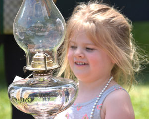 Jenna Smith, 3, checks out an antique glass kerosene lamp.