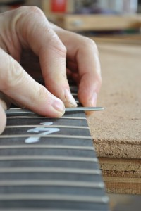 Beckwith works on guitar frets.