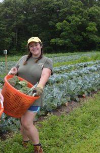 Volunteer Team Leader Jenny Rubin holds her harvest basket during her shift last summer.