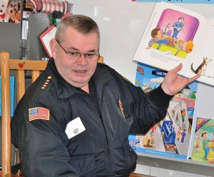 """Police Chief Normand Crepeau Jr. reads """"Officer Buckle and Gloria"""" to second-graders."""