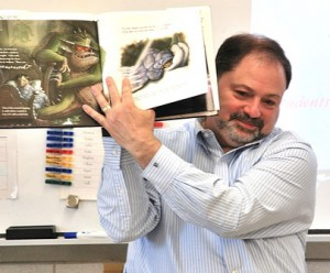 """Lloyd Hamm Jr., president and CEO of Homefield Credit Union, shows fifth-graders illustrations in """"I Need My Monster."""""""