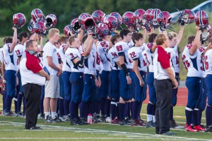 Westborough Rangers football players raise their helmets in salute during the National Anthem