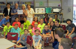 Sixth-graders at the Grafton North Street Elementary School cluster around Phil and Sarah Boyer, founders of the Open Hearts and Minds (OHAM) charity, with Laura Deschenes, the teacher in charge of the project.