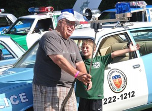 Charlie Melleno and his grandson Graeme Ahern are equipped with a selfie stick to photograph themselves in front of a 1975 Dodge Coronet cruiser from Attleboro.