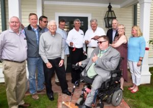 Thomas Hopkins, director of the Mass. Architectural Access Board (in wheelchair), celebrates the grand re-opening of One Grafton Common with local officials and representatives of Apple Tree Arts.