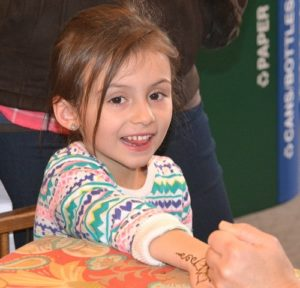 Lyliana Erhartic, 5, gets a glittered Henna tattoo at the Grafton Public Library.