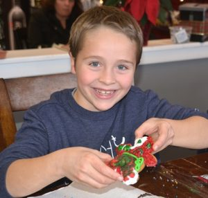 Eddie Cormier, 7, finishes decorating a gingerbread cookie at Bushel N' Peck.