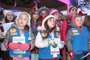 Girl Scouts lead a caroling sing-along.