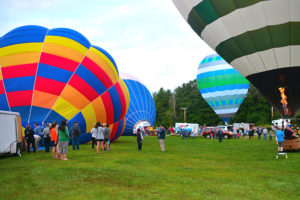 "Festival-goers roam the grounds of Hudson-Concord Elks Lodge 959 early-morning Aug. 19 perusing hot-air balloons named (l to r) ""Equinox,"" ""Big Max,"" ""Break Time"" and ""Celtic Magic."" Photos/Ed Karvoski Jr."