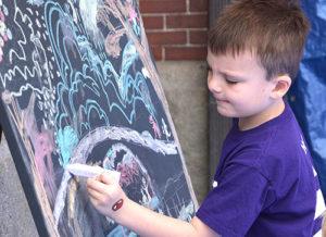 Andrew Murphy, 6, draws on a community art canvas. Photos/Ed Karvoski Jr.