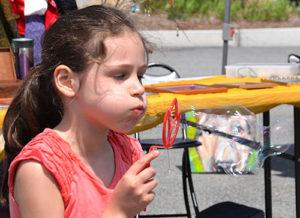 Maria Carrara, 8, blows bubbles in the Main Street Bank parking lot. Photos/Ed Karvoski Jr.