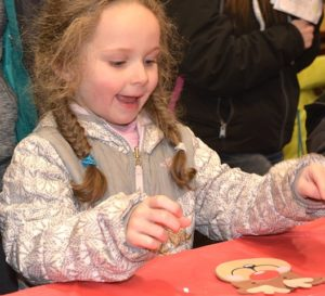 Arianna Russell, 4, makes a Rudolph ornament, offered by Hudson Garden Club at Avidia Bank.