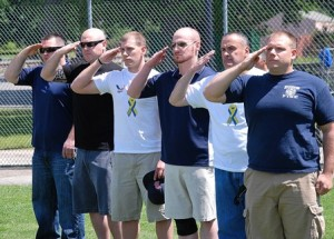 Saluting as the National Anthem is played are representatives from the Hudson Police and Fire Departments, each a Hudson High School alum: (l to r) Ross Hayden, 2007; Jesse Hayden, 1999; Zac Attaway, 2001; Shamus Veo, 2001; Joe Kerrigan, 1986; and Marc Exarhopoulos, 2002.