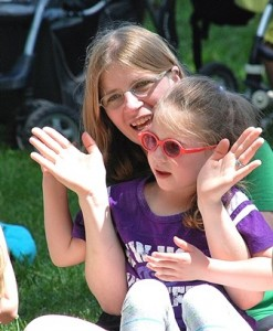Molly Dailey and her daughter, Emma, 5, clap along with songs led by Mister Vic.