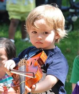 Gabriel Shulman, 2, tries his hand at the violin.