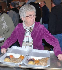 Ellen Auger carries a tray of dinners for delivery.