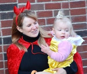 Karen Mercadant, costumed as a devil, holds her granddaughter, Emma Jordan, 22 months, as a princess.