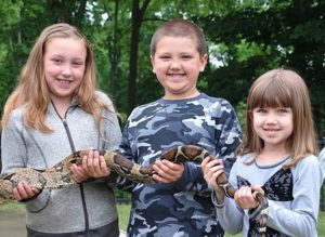 Handling a red-tail boa constrictor provided by Pete's Reptile Experience are (l to r) Kendall Jordan, 8, with her cousins A.J. Leandres, 8, and his sister Lexi, 5.