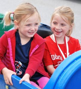 Reese Concannon, 6, and Violet Wintringham, 4, ride in the Happy Wagon.