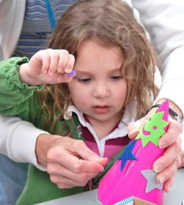 Cassidy Miller, 3, gets help from her grandmother creating a party hat for Hudson's 150th birthday.
