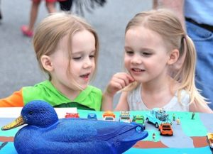 Four-year-old twins Ashlyn and Keira Faherty check an entry in the decorated corporate duck competition.