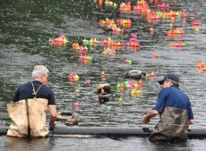 Rotarians Gavin Livingston and Dr. Garrett Sullivan retrieve the first few ducks to cross the finish line.