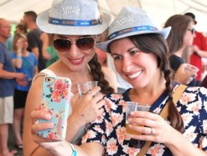 Meghan Hennessey-Hollis and Corie Merhib take a selfie after scoring Samuel Adams hats at last year's Spirit of Hudson Food & Brewfest. (File photo/Ed Karvoski Jr.)