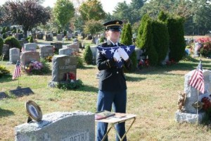A member of the 54th Army Regiment Honor Guard presents the flag.