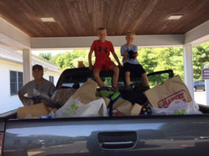 George Luoto (left) and his kids pose by Luoto's truck fully loaded with school supplies to take from Grace Baptist Church to Hudson elementary and middle schools. (Photo/submitted)