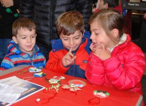 Choosing which ornament to create with help from Hudson Garden Club members at Avidia Bank are the Cabral siblings: Benjamin, 3; Henry, 5; and Evelyn, 7 in this file photo from the 2015 event. File photo/Ed Karvoski Jr.