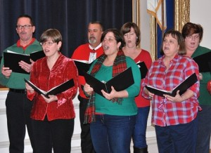 Singing holiday tunes are vocalists of the River's Edge Chorale under the direction of Paul Johnson.