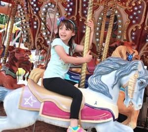 Alexa Amandolare, 5, rides the merry-go-round.