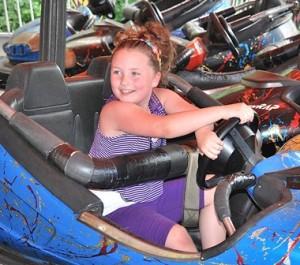 Arianna Sbordone, 7, steers a bumper car.