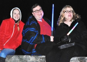 (l to r) Emily Rooney, Kyle Kelly and his mother, Gail, view fireworks from the Morgan Bowl stonewall.