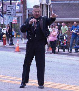 Daniel Clark of the Massachusetts State Police sings before the parade passes through downtown Hudson. Photo/Dakota Antelman