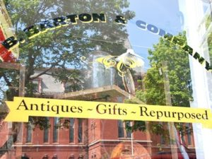 Hudson Town Hall reflects in the window of B. Barton & Company.