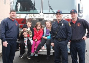 At the C.A. Farley Elementary School drop-off area are (l to r) Firefighter Brian Harrington; A.J. Leandres, 7; holding Jameson Joseph, six months; Lexi Leandres, 5; Kendall Jordan, 7; Firefighters Matt LaBossiere and Brian Sleeper. Photo/Ed Karvoski Jr.