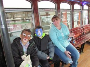 Kal-el Campos (left) and Danny Mosca ride the trolley with Casey Mosca after having their faces painted at one of the trolley stops.