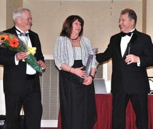 Event co-chairs Bob Kays and Linda Ossing jokingly exchange the gifts given to them by Mayor Arthur Vigeant.