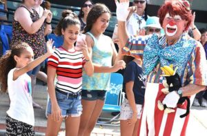 (l to r) Kaylle, 8, Jennifer Silva, 12, and Gabriela Pereira, 12, are happy to greet Smitty of the Aleppo Shriners Clowns on the parade sidelines. Photos/Ed Karvoski Jr.