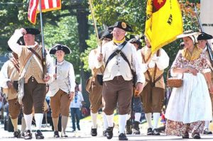The Concord Minute Men Company passes the public library. Photos/Ed Karvoski Jr.