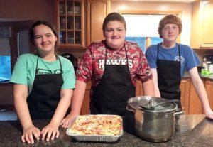 (l to r) Samantha Gogan, Matt Haley and Sam Maston prepare a pasta dinner for a benefit for Aubrey Baumbach.