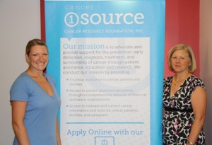 Cancer Resource Foundation Inc.'s Program Coordinator Christina McCarthy (left) and Chief Executive Officer and Co-Founder Mary Lou Woodford stand next to a poster for the 1SourceApp. (Photo/Molly McCarthy)