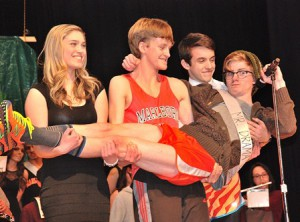 (l to r) Daniela Mahaney, a senior, Austin Turner as Mr. Jazz Band and Peter DiPersio as Mr. Track and Field, assist Evan Dundon, Mr. Drama Club, in the legs competition.