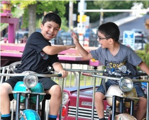 Yonathan Kimyagaron, 7, and his brother Daniel, 5, give each other a high five while riding motorcycles.
